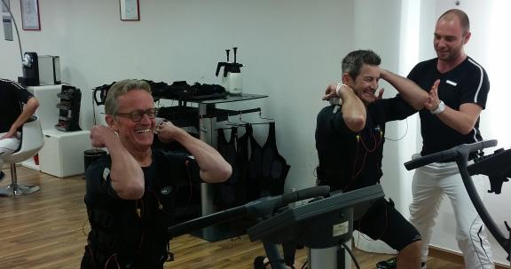 Beste Laune unter Strom: John McGurk und Winfried Beckmann schwitzen unter Anleitung von Body-Street-Filialleiter und -Trainer Philipp Nyhoegen
